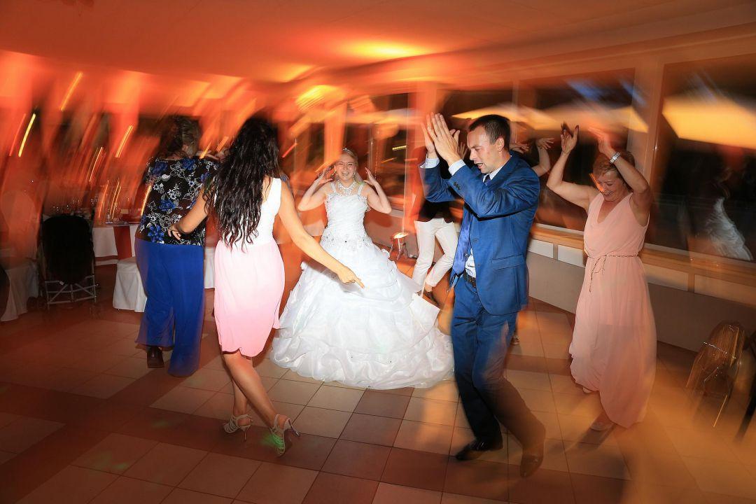 Ausgelassener Tanz der Braut im Brautkleid mit den Gästen, Hochzeitsfotos von Peter Vogel, Hamburg