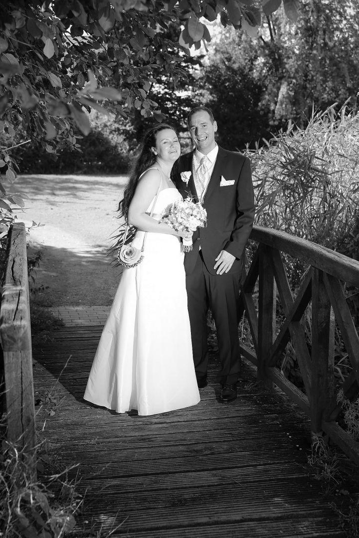 Brautpaar auf Holzbrücke im Park, Schwarzweiß Hochzeitsfoto von Peter Vogel, Hamburg