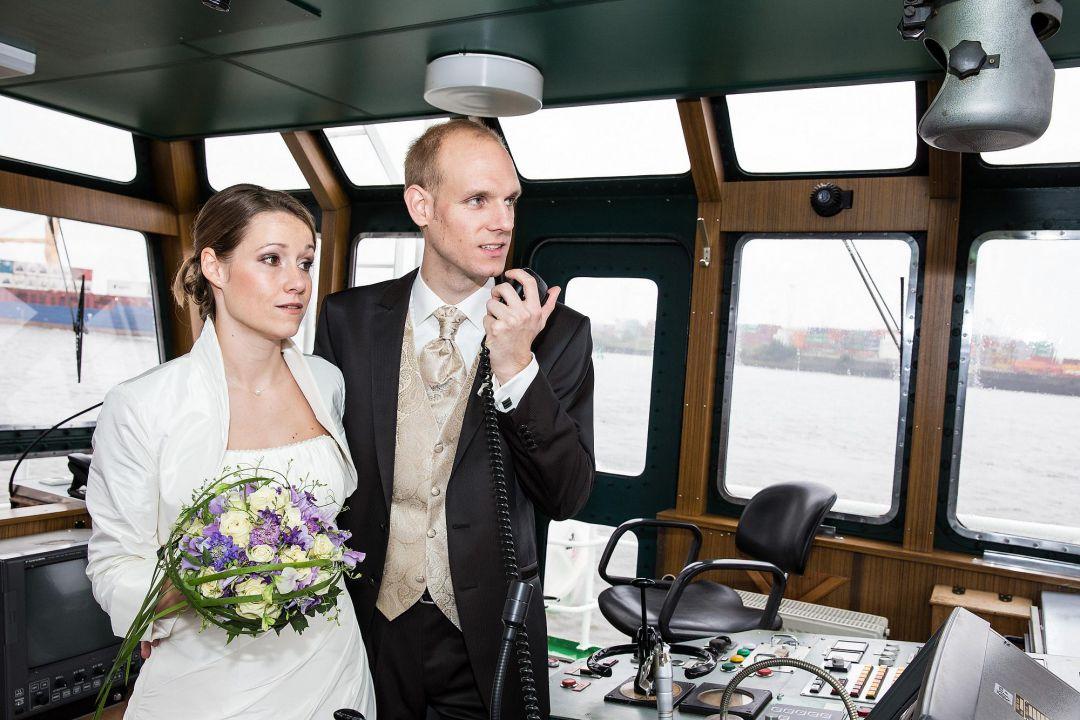 Foto von Brautpaar am Steuerrad eines Kutters im Hamburger Hafen
