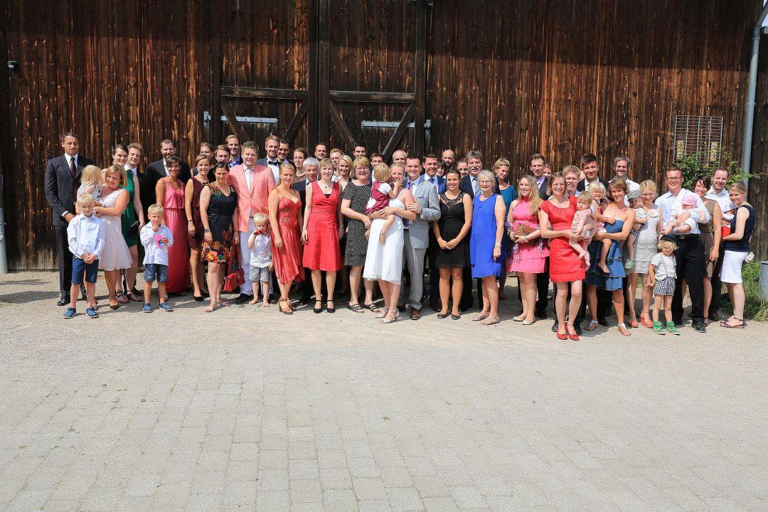 Gruppenbild der Hochzeitsgesellschaft vor rustikalem Hintergrund, Hochzeitsfotos von Peter Vogel, Hamburg