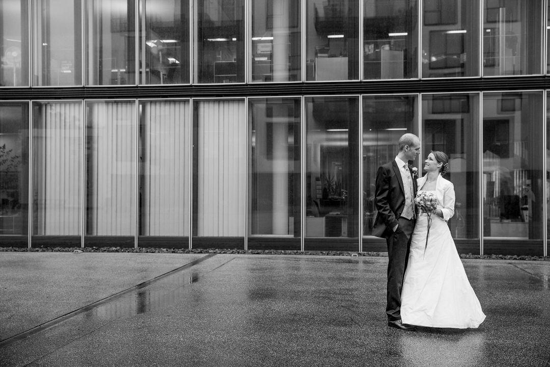 Schwarzweißes Bild vom Brautpaar vor moderner Fassade, Hochzeitsfotos von Peter Vogel, Hamburg