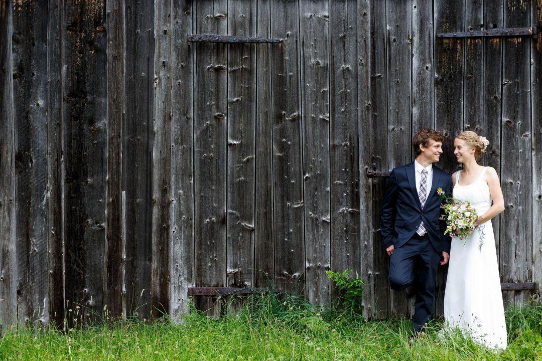 Junges Brautpaar vor rustikaler Holzwand, Hochzeitsfotos von Peter Vogel, Hamburg