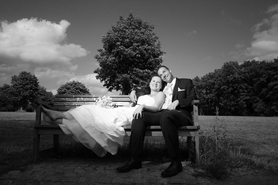 Romantische Szene auf Parkbank mit Brautaar. Schwarzweiß Hochzeitsfotos von Peter Vogel, Hamburg