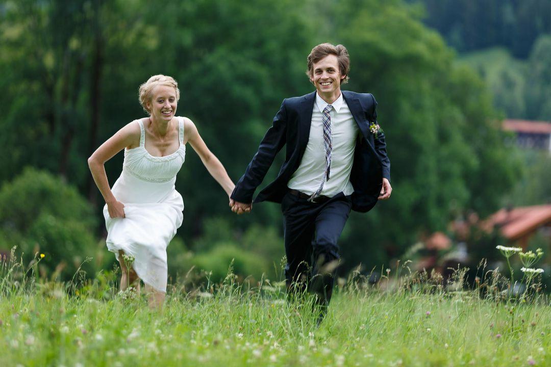 Brautpaar im allgäu läuft über wiese, Hochzeitspaarfotos von Peter Vogel, Hamburg