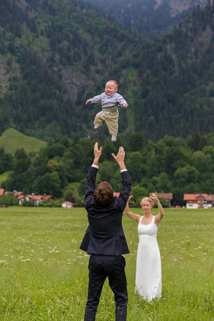Das Brautpaar wirft sich (seinbar) ihr Baby zu, Hochzeitsfotos von Peter Vogel, Hamburg