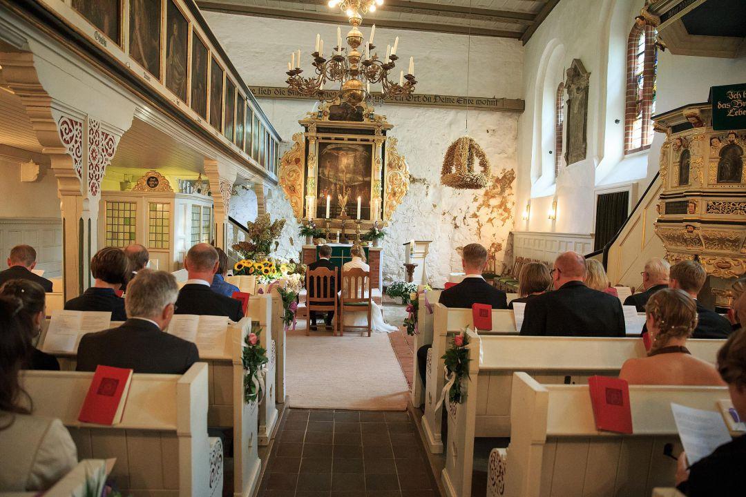 Bild von einer kirchlichen Trauung zeigt das Brautpaar vor dem Barocken Altar