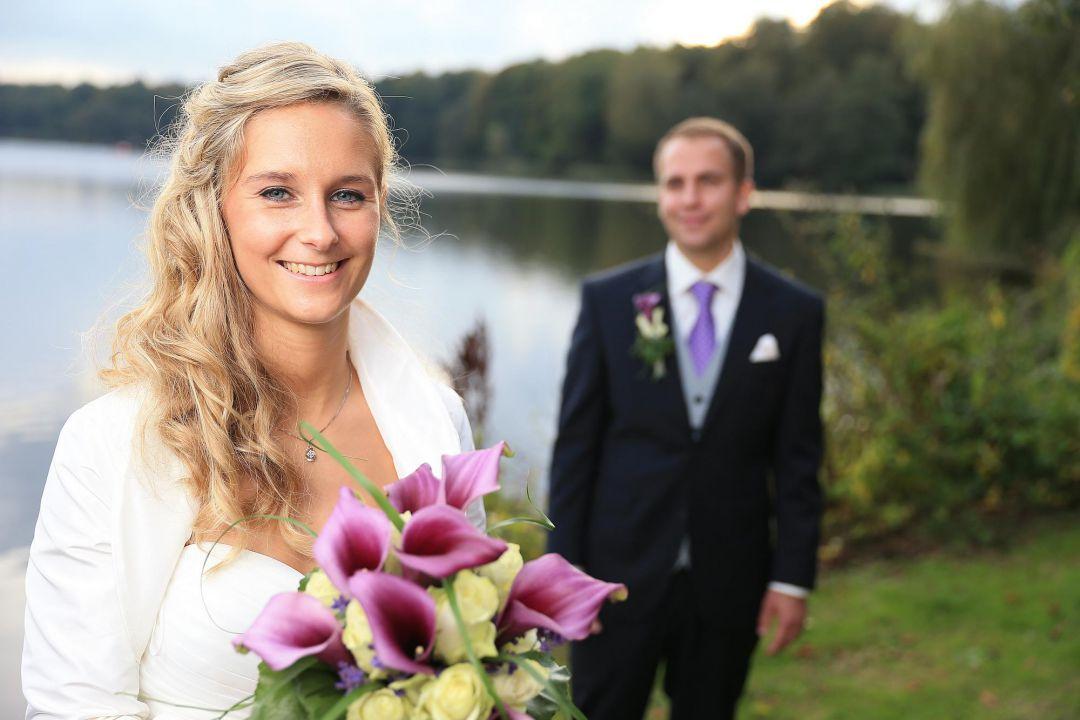 Bild vom Brautpaar vor einem See mit glücklicher Braut, Hochzeitsfotos von Peter Vogel, Hamburg