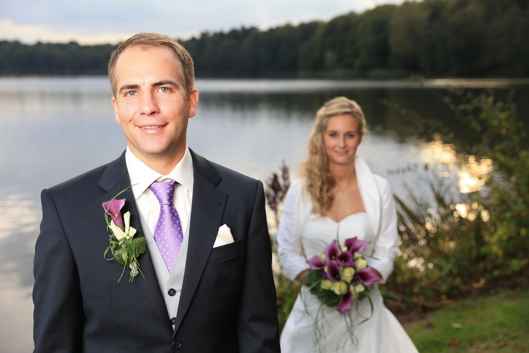 Bild vom Brautpaar vor einem See mit strahlendem Bräutigam, Hochzeitsfotos von Peter Vogel, Hamburg