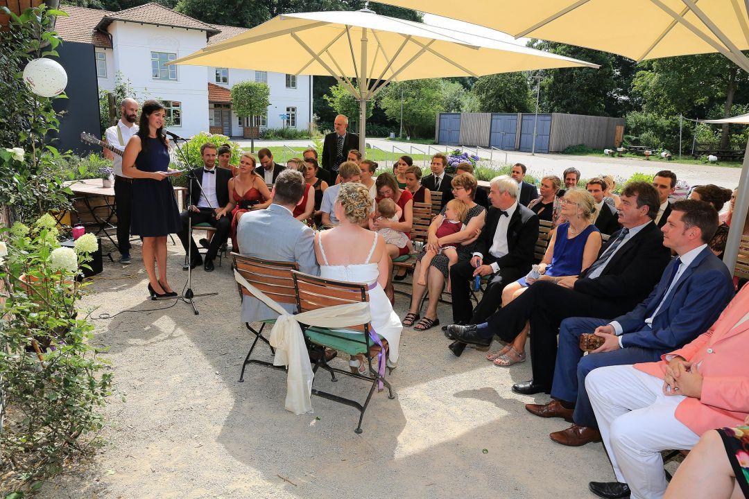 Szene einer sommerlichen Trauung im Freien mit Hochzeitspaar und hochzeitsgästen