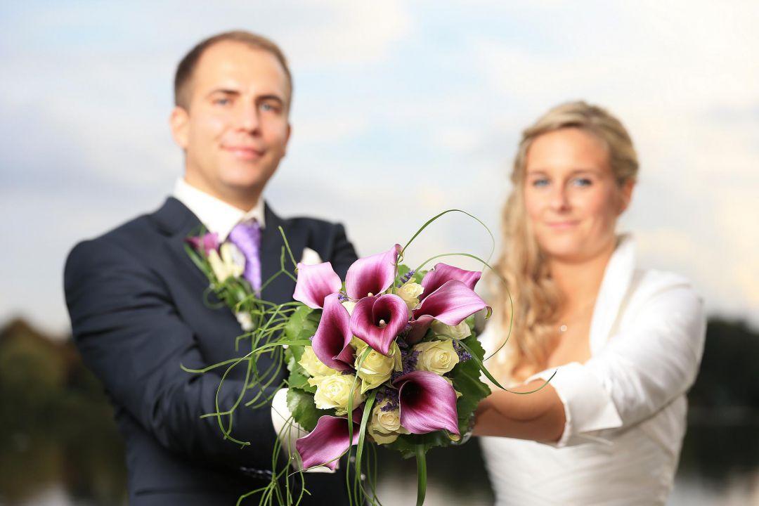 Brautpaar präsentiert den Brautstrauß, Hochzeitsfotos von Peter Vogel, Hamburg