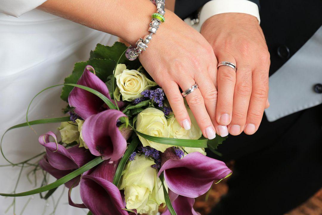 Brautpaar zeigt die Trauringe auf dem Brautstrauß, Hochzeitsfotos von Peter Vogel, Hamburg
