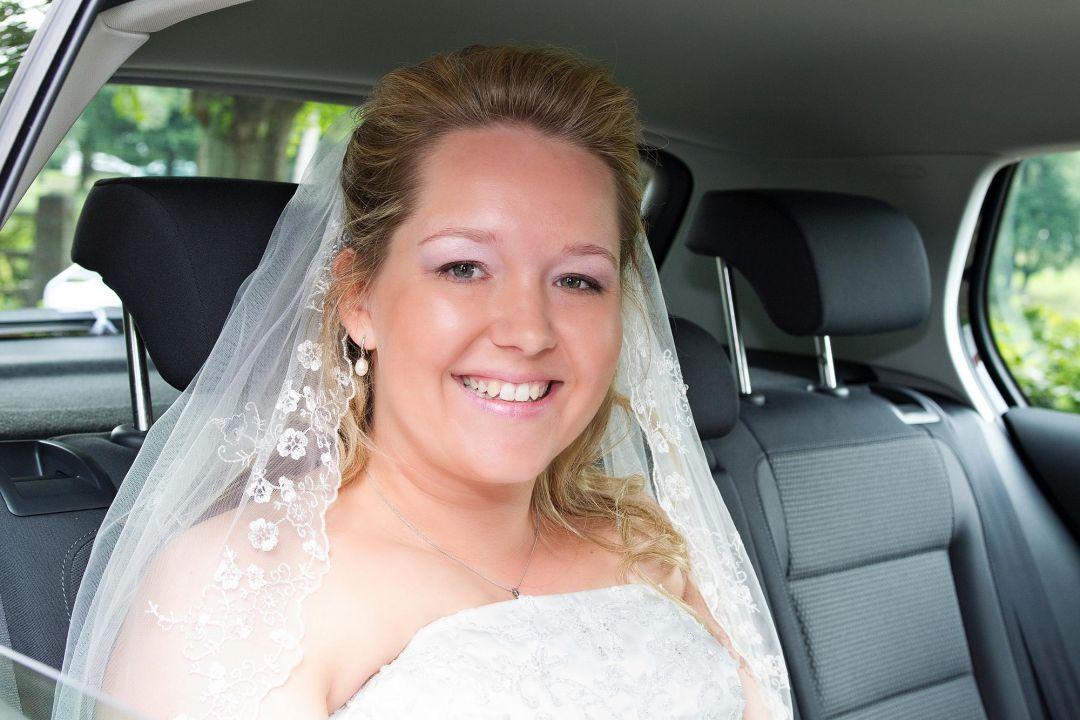Junge Braut im Auto lächelt in die Kamera. Hochzeit Fotograf Hamburg Peter Vogel