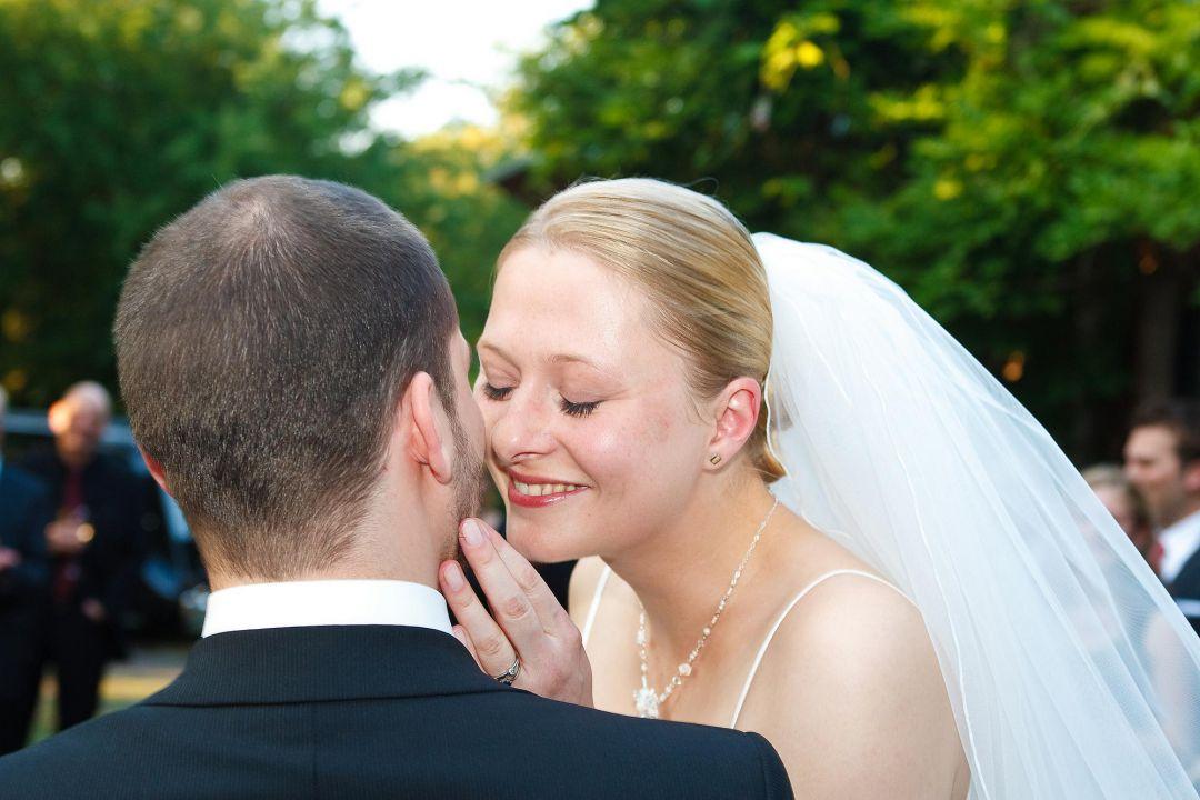 Junge Braut im weißen Brautkleid mit Schleier küßt Bräutigam. Hochzeitsfoto von Peter Vogel