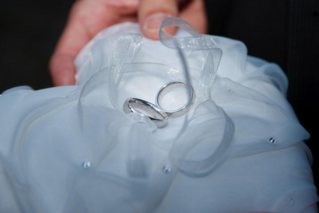 Braut zeigt Eheringe auf weißem Tuch, Hochzeitsfotos von Peter Vogel, Hamburg