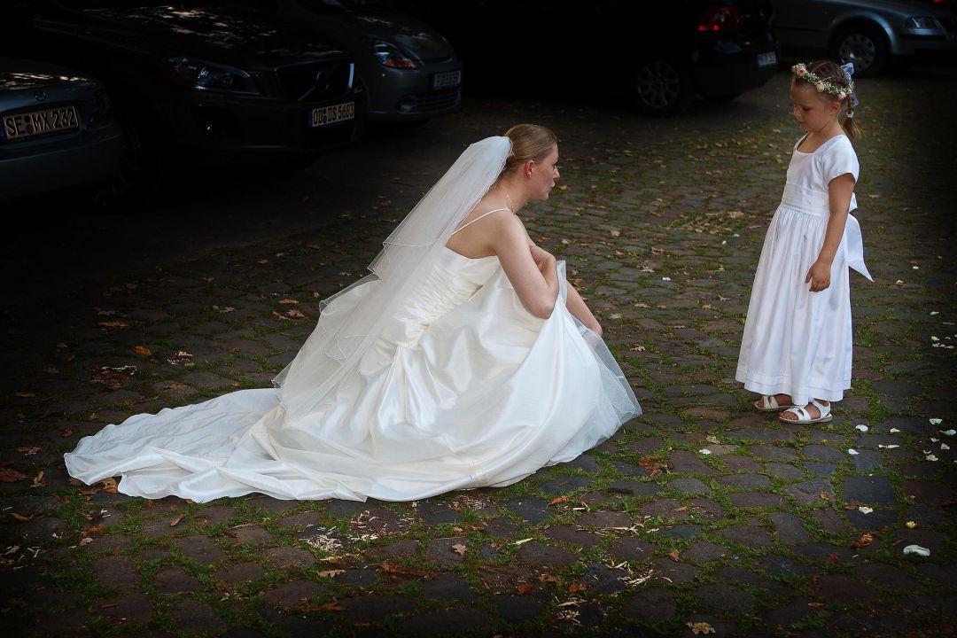 Braut im weißen Brautkleid tröstet kleinen Gast, Hochzeitsfotos von Peter Vogel, Hamburg