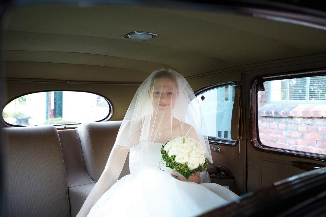 Junge Braut mit Schleier im historischen Auto auf dem Weg zur Trauung, Hochzeitsfotos von Peter Vogel, Hamburg