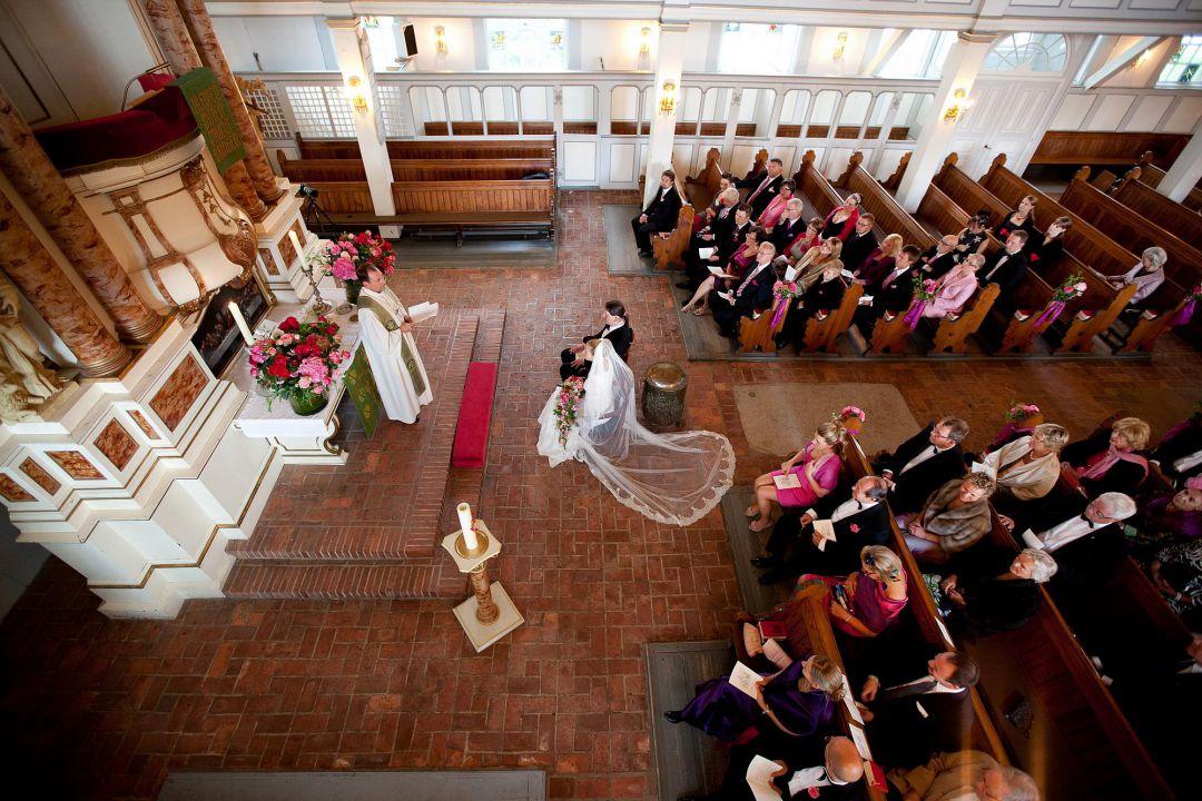 Hochzeit in einer historischen Kirche, Bild von oben auf den Altar mit Brautpaar und Pfarrer. Hochzeitsfoto von Peter Vogel