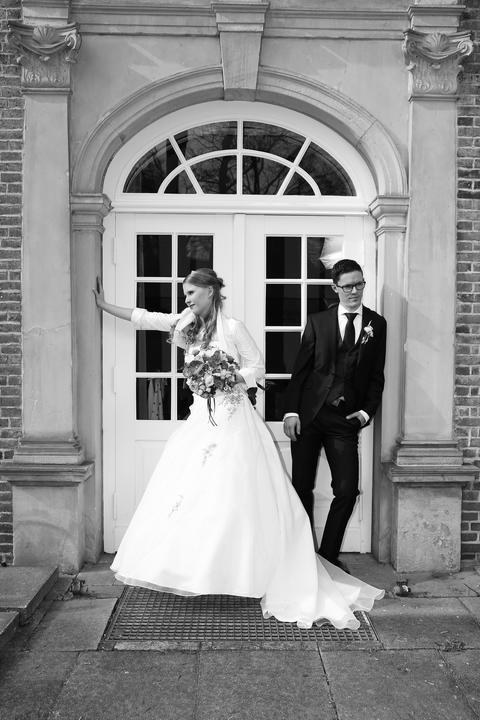 Abwechslung beim Brautpaarfoto: Spielfreudiges Brautpaar in schwarz weiß